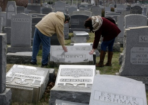 Joe Nicoletti and Ronni Newton of the Taconey Holmesburg town watch group pay their respects at a damaged headstone in Mount Carmel cemetery Monday, Feb. 27, 2017, in Philadelphia. (AP Photo/Jacqueline Larma)