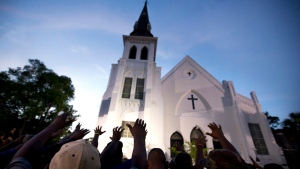 The men of Omega Psi Phi Fraternity Inc. lead a crowd of people in prayer outside the Emanuel AME Church, after a memorial for the nine people killed by Dylann Roof in Charleston, S.C. on June 19, 2015. (Stephen B. Morton/AP)