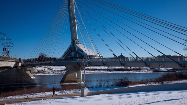 A woman runs on a path along the Assiniboine River as the Provencher pedestrian bridge towers above her in Winnipeg, Man., on November 30, 2015. (Darryl Dyck/The Canadian Press)