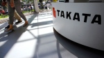 In this May 4, 2016, file photo, visitors walk by a Takata Corp. desk at an automaker's showroom in Tokyo. (AP Photo/Shizuo Kambayashi, File)