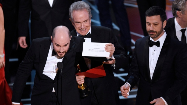 """Jordan Horowitz, producer of """"La La Land,"""" shows the envelope revealing """"Moonlight"""" as the true winner of best picture at the Oscars on Sunday, Feb. 26, 2017, at the Dolby Theatre in Los Angeles. Presenter Warren Beatty and host Jimmy Kimmel look on from right. (Chris Pizzello/Invision/AP)"""