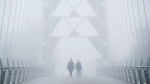 People walk on the Humber Bay Arch Bridge during heavy fog in Toronto, Wednesday February 22, 2017. THE CANADIAN PRESS/Mark Blinch
