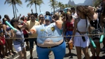 "A woman dressed in an Officer Pudge inflatable costume joins in the, ""If you don't give me....then you lend me"" carnival street party on Ipanema beach, in Rio de Janeiro, Brazil, Sunday, Feb. 19, 2017.  (AP / Silvia Izquierdo)"