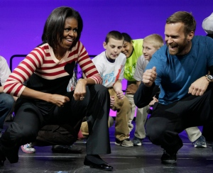 In this Feb. 9, 2012, file photo, first lady Michelle Obama and Bob Harper of 'The Biggest Loser,' right in blue shirt, do the Interlude dance during a Let's Move event with children from Iowa schools at the Wells Fargo Arena in Des Moines, Iowa. (AP Photo/Carolyn Kaster, File)