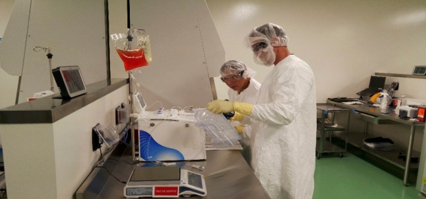 In this May 2016 photo provided by Kite Pharma, cell therapy specialists at the company's manufacturing facility in El Segundo, Calif., prepare blood cells from a patient to be engineered in the lab to fight cancer. (Kite Pharma via AP)