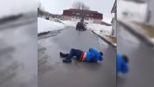 This screengrab shows a man lying on the ground after he was hit by an Audi SUV in Saint John, N.B. that was caught on film. (GhettoNewBrunswick SJ / YouTube)