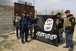 Iraq's federal police forces celebrate as they hold a flag of the Islamic State group they captured after regaining control of Gawsaq neighborhood in the western side of Mosul, Iraq, Monday, Feb. 27. 2017. (AP / Mohammed Saad)