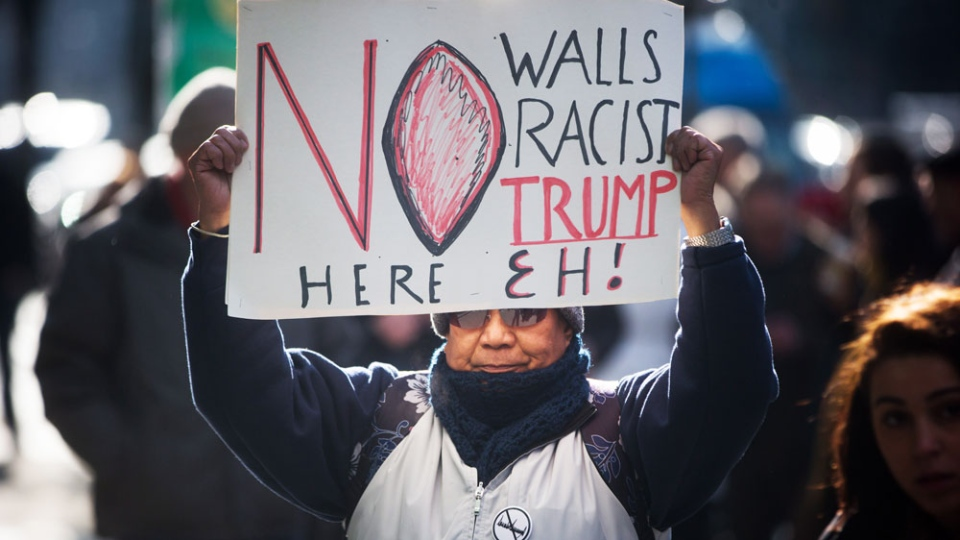 A protester carries a sign outside the official opening of the Trump International Hotel and Tower in Vancouver, B.C., on Tuesday Feb. 28, 2017. U.S. President Donald Trump's sons Donald Jr. and Eric attended the opening. (THE CANADIAN PRESS/Darryl Dyck)