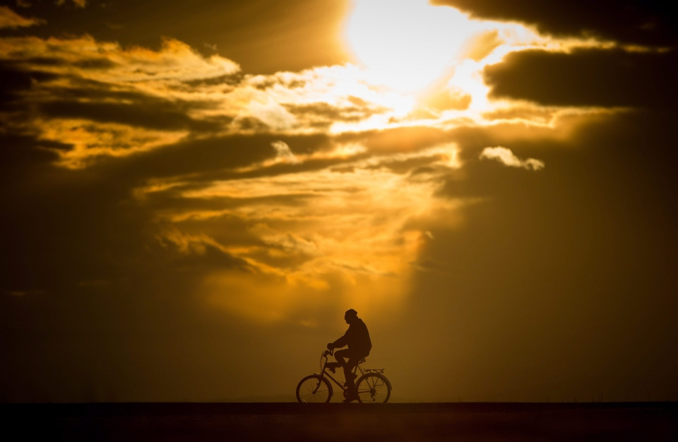 A man is silhouetted while riding a bike at Garry Point Park at sunset in Richmond, B.C., on Monday, February 27, 2017. (Darryl Dyck / THE CANADIAN PRESS)