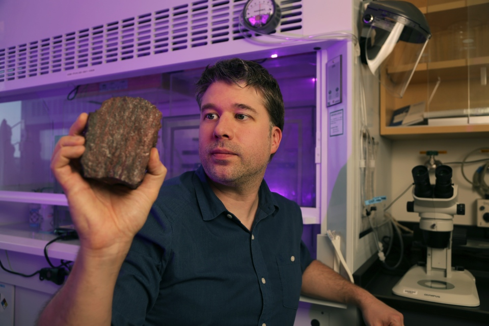 Johnathan O'Neil, assistant professor at the University of Ottawa's Department of Earth and Environmental Sciences, holds a sample of rock taken from the area where he and the research team discovered microfossils of the oldest life forms ever found on earth. Photo by Dave Weatherall. (University of Ottawa)