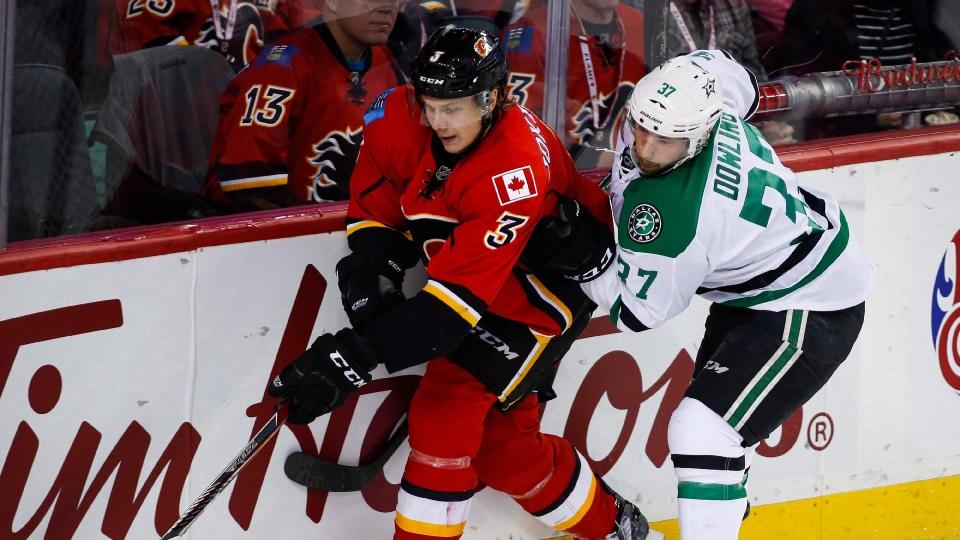 Dallas Stars' Justin Dowling, right, checks Calgary Flames' Jyrki Jokipakka, from Finland, during second period NHL hockey action in Calgary, Thursday, Nov. 10, 2016.THE CANADIAN PRESS/Jeff McIntosh