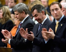 Prime Minister Stephen Harper, Jim Prentice, Minister of Environment, and Minister of National Defence Peter MacKay, left to right, rise to pay tribute to late photojournalist Tom Hanson in the House of Commons following question period on Parliament Hill in Ottawa on Wednesday March 11, 2009. (Sean Kilpatrick / THE CANADIAN PRESS)