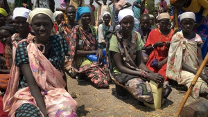 In this photo taken Wednesday, March 1, 2017, women sit in line on the ground waiting to receive food distributed by the World Food Program (WFP) in Padeah, South Sudan. (AP Photo / Sam Mednick)
