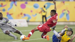Canada's Raheem Edwards shoots against Brazil's goaltender Andrey Da Silva and falling defender Luan Garcia during the second half of men's soccer action at the Pan Am Games in Hamilton on Sunday, July 12, 2015. THE CANADIAN PRESS/Peter Power