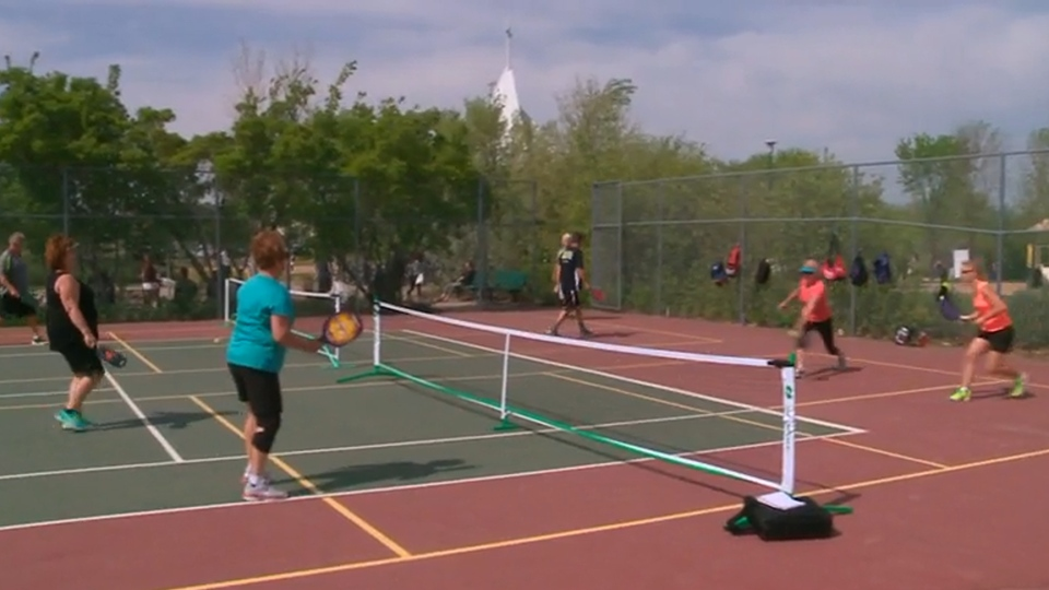 Four women compete in a friendly game of pickleball, a popular racquet sport that combines elements of tennis, badminton and ping pong.