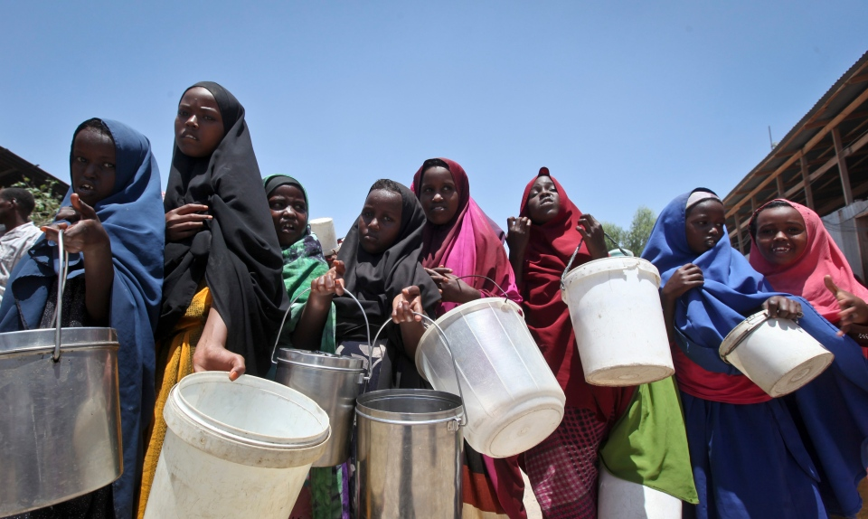 In this Saturday, Feb. 25, 2017 file photo, displaced Somali girls who fled the drought in southern Somalia stand in a queue to receive food handouts at a feeding center in a camp in Mogadishu, Somalia. (AP Photo/Farah Abdi Warsameh, File)
