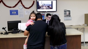 An official for the Consulate General of Mexico in San Diego works with a family Friday, March 3, 2017, in San Diego. (AP Photo/Gregory Bull)