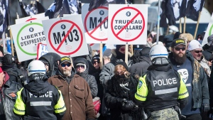 Police hold back protesters during a demonstration regarding motion M-103 in Montreal, Saturday, March 4, 2017. THE CANADIAN PRESS/Graham Hughes