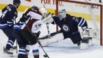 Winnipeg Jets goalie Connor Hellebuyck (37) gets his arm to this shot by Colorado Avalanche's John Mitchell (7) as Jets' Paul Postma (4) and Ben Chiarot (7) defend during third period NHL action in Winnipeg on Saturday, March 4, 2017. THE CANADIAN PRESS/John Woods