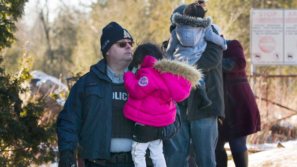 An RCMP officer escorts a family as they cross the U.S.-Canada border in Hemmingford, Que., on Sunday, March 5, 2017. (THE CANADIAN PRESS/Graham Hughes)