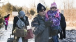 An RCMP officer escorts a woman and a child claiming to be from Yemen as they cross the U.S.-Canada border in Hemmingford, Que. on Sunday, March 5, 2017. (Graham Hughes / THE CANADIAN PRESS)