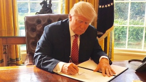 U.S. President Donald Trump signs an executive order issuing a revised travel ban on Monday, March 6, 2017.
