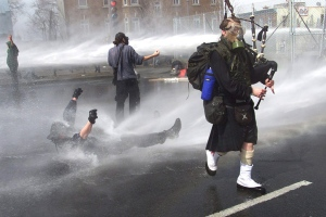 A masked bagpiper plays his way though water from police cannons as other protesters are sprayed outside the site of the Summit of the Americas in Quebec City Saturday, April 21, 2001 in this photo by Canadian Press photographer Tom Hanson. (Tom Hanson / THE CANADIAN PRESS)