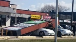 The strong wind blew a sign at a Chatham strip mall on St. Clair Street on top of two vehicles on Wednesday, March 3, 2017.