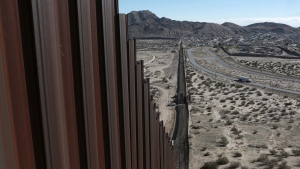 FILE - In this Wednesday, Jan. 25, 2017 file photo, a truck drives near the Mexico-U.S. border fence, on the Mexican side, separating the towns of Anapra, Mexico and Sunland Park, New Mexico. (AP Photo/Christian Torres)