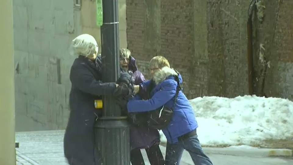 A group of women hold onto a light post in St. John's, Newfoundland and Labrador. (CTV News)