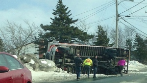 People look on as a truck lies on its side in Paradise, N.L. on Saturday, March 11, 2017 in this handout photo. (THE CANADIAN PRESS/HO, Troy Mitchell)