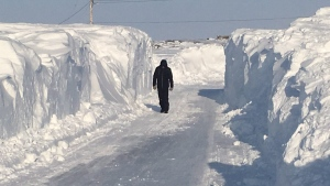 A person walks down a plowed street, surrounded by snow walls, in Churchill, Man., on Saturday, March 11, 2017. (THE CANADIAN PRESS/HO-Shane Hutchins)