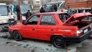 In this photo released by the Syrian official news agency SANA, people inspect the damage to a parking lot at the site of an attack by twin explosions in Damascus, Syria, Saturday, March 11, 2017. (SANA via AP)