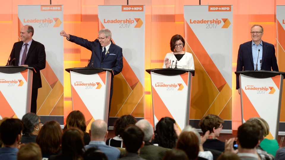 Guy Caron, left, Charlie Angus, Niki Ashton and Peter Julian react to the audience as they arrive on stage for the first debate of the federal NDP leadership race, in Ottawa on Sunday, March 12, 2017. THE CANADIAN PRESS/Justin Tang
