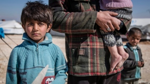 In this picture taken, Feb. 16, 2017, a Syrian school teacher from Deir Ezzour, stands with his son and daughter in Al Hol Camp, Hasakah Governorate, Syria. (Photo Courtesy: Jonathan Hyams, Save the Children via AP)