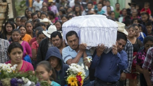 People carry the coffin of 14-year-old Ana Roselia Perez Junay, who died in a fire at a children's shelter, to the cemetery in Zaragoza, Guatemala on Sunday, March 12, 2017. (AP / Moises Castillo)