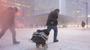 A person makes their way across King Street as snow flies through the air during a squall in downtown Toronto's financial district, on December 15, 2016. (Graeme Roy/The Canadian Press)