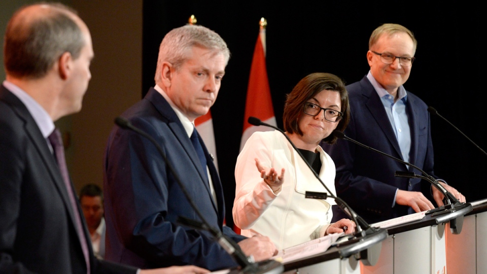 Niki Ashton, second from right, speaks with Guy Caron, left, as Charlie Angus and Peter Julian look on during the first debate of the federal NDP leadership race, in Ottawa on March 12, 2017. (Justin Tang / THE CANADIAN PRESS)