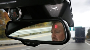 A Mobileye camera system to monitor speed limits and warn drivers of potential collisions, mounted behind the rearview mirror of a vehicle in Ann Arbor, Mich. (AP / Carlos Osorio)