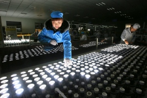 In this photo taken Tuesday Feb. 28, 2017, a worker tests LED lights at a factory in Suining city in southwestern China's Sichuan province. (Chinatopix)