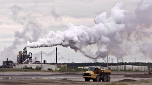 A dump truck works near the Syncrude oil sands extraction facility near the city of Fort McMurray, Alta., in this file photo from June 1, 2014. THE CANADIAN PRESS/Jason Franson