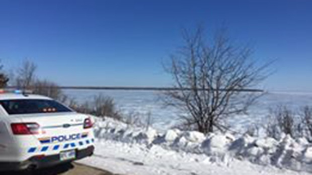 A police car is shown at the edge of Lake Winnipeg, in Manitoba, after a vehicle went through the ice on March 14, 2017. (Ko'ona Cochrane / Facebook)