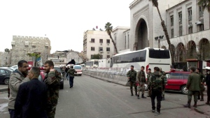 In this photo released by the Syrian official news agency SANA, Syrian security forces gather in front the main judicial building which attacked by a suicide bomber, in Damascus, Syria, Wednesday, March 15, 2017. (SANA via AP)