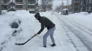 Lacking a shovel, a man clears his car off with a hockey stick.