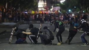Gas mask wearing demonstrators take cover as they face off with police as they protest government proposed changes to work rules and pensions in Rio de Janeiro, Brazil on Wednesday, March 15, 2017. (AP / Leo Correa)