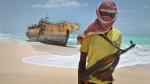 Masked and armed Somali pirate Hassan stands near a Taiwanese fishing vessel washed ashore after the pirates were paid a ransom and the crew were released in the once-bustling pirate den of Hobyo, Somalia on Sunday, Sept. 23, 2012 . (AP)