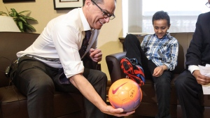 Alberta Finance Minister Joe Ceci presents a new pair of soccer shoes to 11-year-old Yusef Moalim during a pre-budget photo opportunity in Edmonton, Alta., on Tuesday March 14, 2017. (Jason Franson / THE CANADIAN PRESS)
