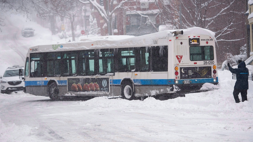 A city bus is helped out of a snow bank after getting stuck following a winter storm in Montreal, on Wednesday, March 15, 2017. (THE CANADIAN PRESS/Graham Hughes)