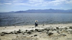 A man fishes for tilapia along the receding banks of the Salton Sea near Bombay Beach, Calif. on April 30, 2015. (AP / Gregory Bull)