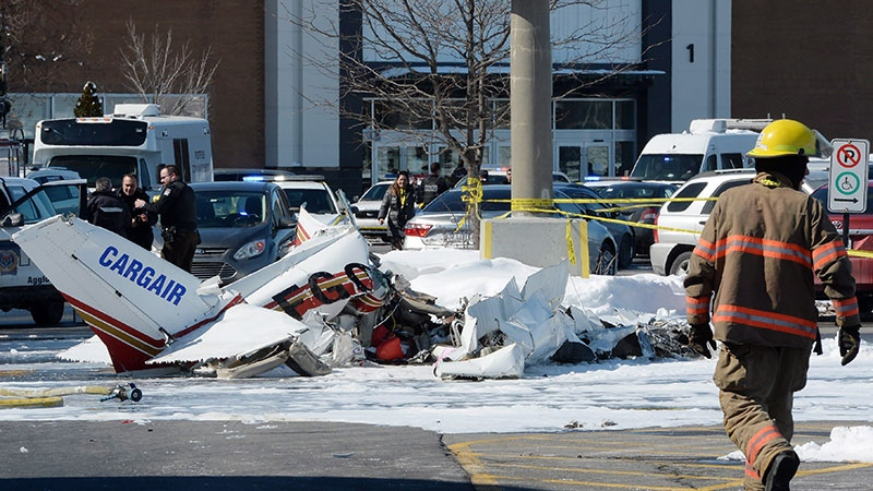A firefighter and police officers look at the wreckage from a plane crash sits in a parking lot in Saint-Bruno, Que., on Friday, March 17, 2017. (THE CANADIAN PRESS/Ryan Remiorz)